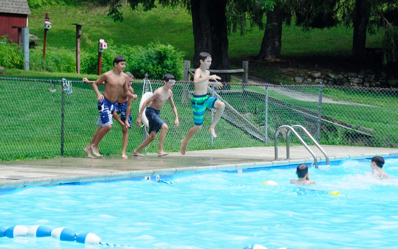 Campers jumping in the pool