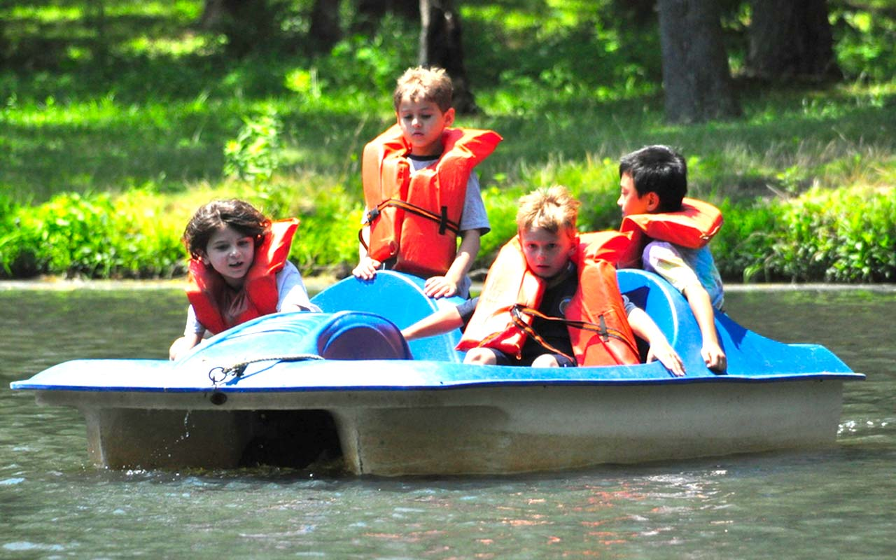 Campers in a paddle boat on the lake